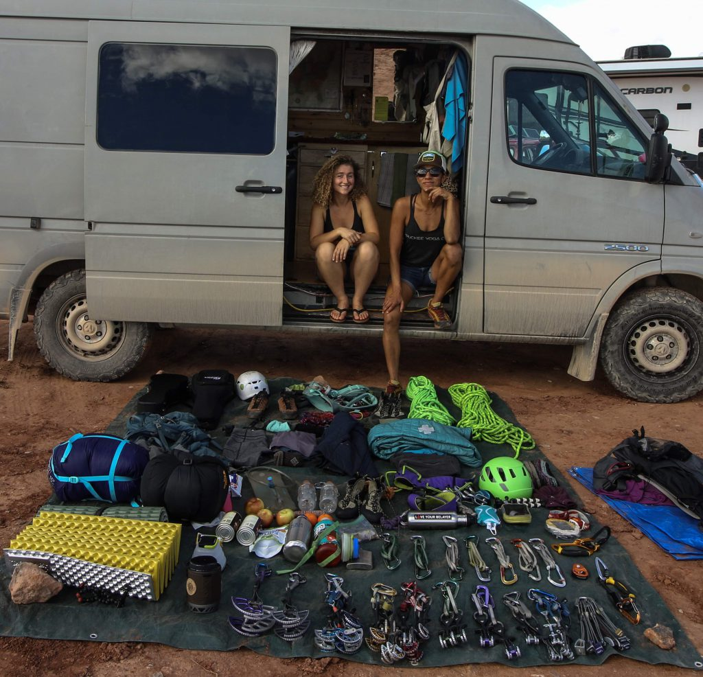 Kaya Lindsay and Dani Reyes-Acosta sitting in front of their gear for an overnight climb